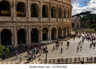 Rome, Italy - September 14 2017: Colosseum external view with visitors. Tourists outside the Roman amphitheater entrances with barriers.
