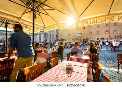 Rome, Italy - September 16 2019: Tourists dine at a romantic Italian restaurant as the sun goes down and they watch the activity in Piazza Navona in Rome Italy