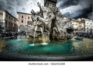 Rome, Italy - September 20 2016: The Fountain of the Four Rivers by Bernini in the Piazza Navona in Rome Italy as the skies darken with a storm approaching.