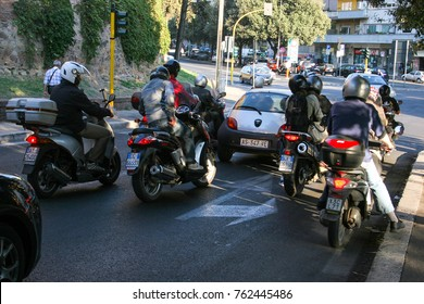 Rome / Italy - September 2011: typical picture on streets of Rome, many motorcycles and a small white car are waiting for the traffic light