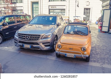 ROME, ITALY - September, 2018: cityscape. two cars at parking lot: small orange fiat and grey large mercedes benz