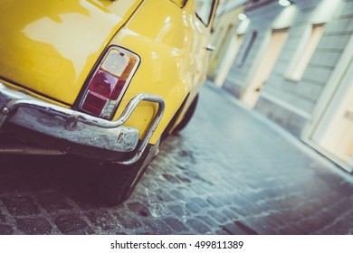 Rome, Italy - September 22, 2015: Closeup view of a yellow Fiat 500 parked in the historical centre of Rome. The Fiat 500 is a rear-engine, four passenger city car manufactured by Fiat Automobiles.