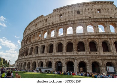 ROME, ITALY - SEPTEMBER 24, 2015 : View of ancient amphitheatre of Colosseum built by Vespasian and Titus in Rome with people around, on cloudy blue sky background.