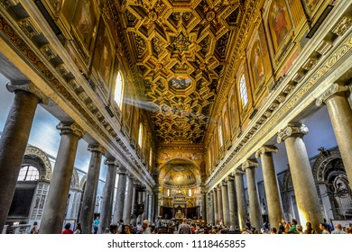 Rome, Italy - September 24 2017: Tourists visit the Basilica of Our Lady in Trastevere cathedral to appreciate the ornate golden interior in the Trastevere section of Rome, Italy