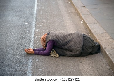 ROME, ITALY - SEPTEMBER 26,2018: The beggar lies on the street of Rome and asks for alms