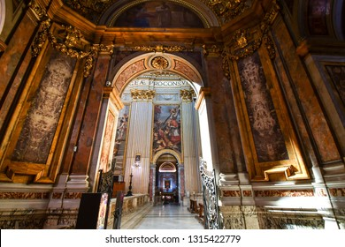 Rome, Italy - September 29 2018: View looking through doorway of a small chapel to the golden, ornately decorated interior napse and apse of the Basilica of Sant'Andrea della Valle in Rome, Italy.