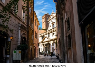 Rome, Italy - September 30 2018: Tourists walk past shops down a shaded back alley towards the Saint Eustace Church with the White Stag sculpture on it's roof in the historic center of Rome, Italy
