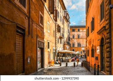 Rome, Italy - September 30 2018: A woman walks through an empty back alley towards a sidewalk cafe and small piazza in the historic center of Rome, Italy