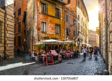 Rome, Italy - September 30 2018: Tourists pass through an alley by a picturesque Italian hostaria sidewalk cafe as they head towards a piazza in Rome, Italy.