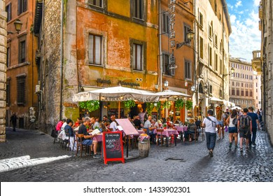 Rome, Italy - September 30 2019: Tourists enjoy lunch on a summer day at an Italian sidewalk cafe restaurant in an alley near the historic center of Rome, Italy.