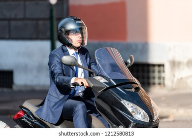 Rome, Italy - September 4, 2018: One local Italian man riding scooter motorcycle moped in city street closeup, commute commuting to work business office in suit, businessman