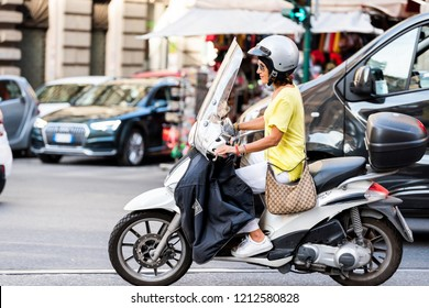 Rome, Italy - September 4, 2018: One local Italian woman riding scooter motorcycle moped in city street traffic closeup, happy smiling