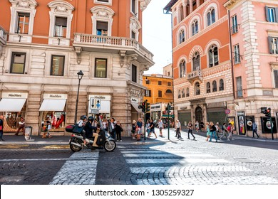 Rome, Italy - September 5, 2018: Italian street intersection outside in historic city sunny day and busy shopping stores with people on motorcycle scooter