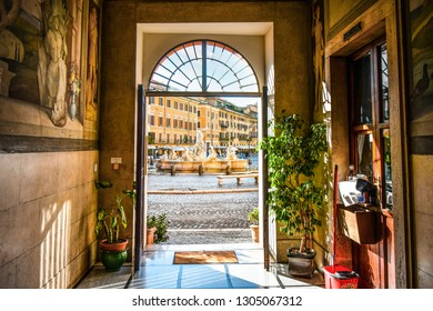 Rome, Italy - September 9 2018: View of the Neptune Fountain with cafes behind from inside a doorway of a medieval building on the Piazza Navona in Rome, Italy