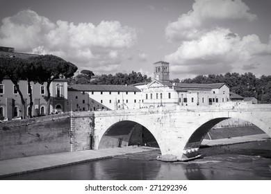 Rome, Italy. Tiber Island (Isola Tibertina), view of Basilica of St. Bartholomew on the Island. Ripa district. Black and white retro style - monochrome color tone.