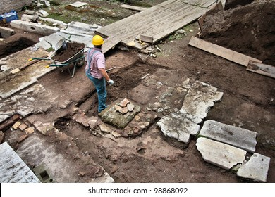 Rome, Italy - UNESCO World Heritage Site. Excavation worker digging around ancient Roman monument. Archeologist at work.