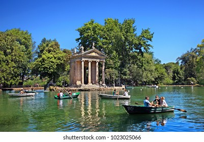 """ROME, ITALY- Visitors rowing their boats in the lake of the Villa Borghese gardens, next to the 18th century """"Temple of Asclepius (Aesculapius)."""