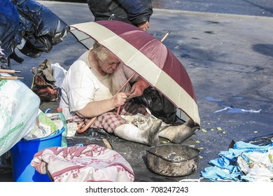 ROME, ITALY-August 22 : Homeless old woman sitting with red umbrella in the street on August 22,2014
