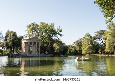 Rome - July 17th 2014: Horizontal view of Aesculapius temple located in Villa Borghese surrounded by vegetation on a sunny day.  Boats with tourists floating in the pond.