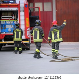 Rome, RM, Italy - May 10, 2018: three Italian firefighters and the fire truck  with uniform and text Vigili del fuoco that means Firemen in Italian language . The fireman with red helmet is the leader
