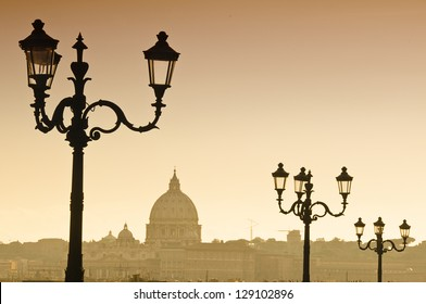 Rome skyline in Italy seen from Villa Borghese garden. The dome of Saint Pierre Basilica in Vatican in the distance. Street lamps in the foreground