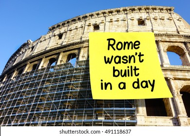 Rome wasn't built in a day idiom note affixed on Colosseum in Rome, Italy