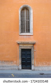 Rome/Italy - February 24, 2012:  Ancient orange building in Rome. The big black door is closed, a huge window is located above it. The street is empty.