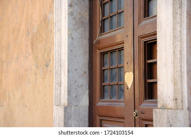Rome/Italy - February 24, 2012:  Ancient brown wooden door of one of the old houses of Rome. There is a window with bars on the door. Heart sticker on the door