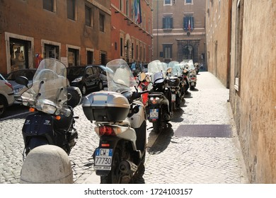 Rome/Italy - February 24, 2012: Deserted street of Rome on a sunny morning. There are a lot of motorcycles and scooters parked on the street.
