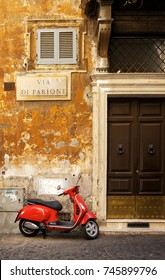 ROME,ITALY - JULY 17,2017 : Old narrow street in Rome with a typical red vespa scooter on a cobblestone street