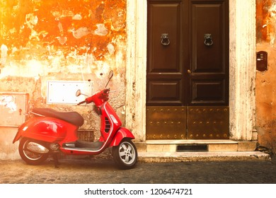 ROME.ITALY - JULY 21, 2017 : Street scene with a red scooter on an old narrow street in Rome