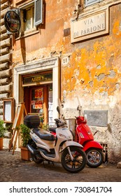 ROME.ITALY - JULY 21, 2017 : Typical street scene in Rome with scooters on an old narrow cobblestoned street