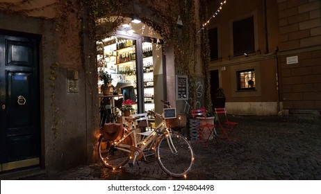 ROME,ITALY,13TH JANUARY,2019. There is a street in Rome.In this street, you can see a wine house and also there is a bike which has got lights around it.You may taste very delicious wine experience