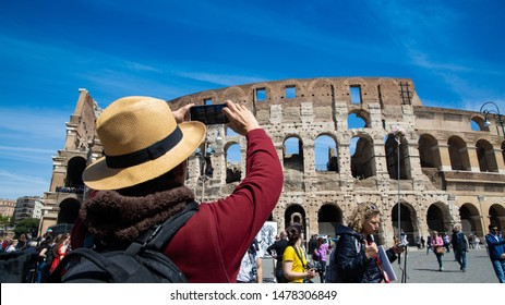ROME-ITALY-MAY-19-2019:Young man with hat take a picture by smartphone at Colosseum in Rome landmark which Rome Colosseum is one of the best known monuments of Rome and Italy