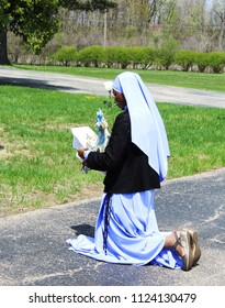 Romulus, MI/USA: May 6, 2018 – Catholic nun kneels during outdoor ceremony to honor the Blessed Virgin Mary at a May Crowning ceremony. May is the month of Mary, mother of Jesus, in the Catholic faith