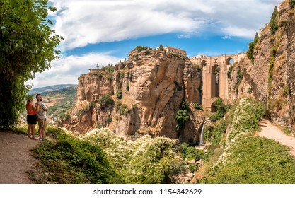 Ronda, Spain. Circa July 2018.Couple of tourists enjoying the views of the Puente Nuevo bridge and the houses built on the edge of the cliff, in the ancient city of Ronda, Spain