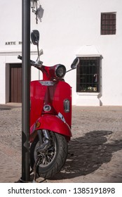 Ronda, Spain, February 2019. An old Italian red scooter is parked near the main attraction of Ronda - the bullring. Plaza de Toros.