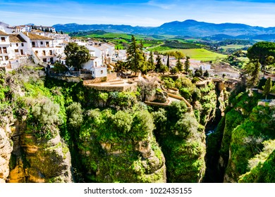 Ronda, Spain: Landscape of white house on the green edges of steep cliffs with mountains in the background.
