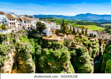 Ronda, Spain: Landscape of white houses on the green edges of steep cliffs with mountains in the background.