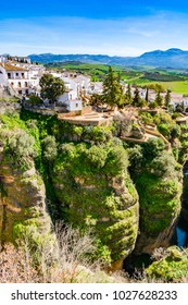 Ronda, Spain: Landscape of white houses on the green edges of steep cliffs with mountains in the background. on the green edges of steep cliffs with mountains in the background.