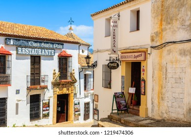 RONDA, SPAIN - MAY 10, 2018: Shops and small restaurants in narrow streets of Ronda village, Andalusia, Spain. This place is famous tourist destination.