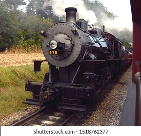 Ronks, Pennsylvania USA September 28, 2019 Strasburg Railroad A front quarter view of the Norfolk & Western Class M #475 passing a passenger train amidst smoke and steam at a switch point