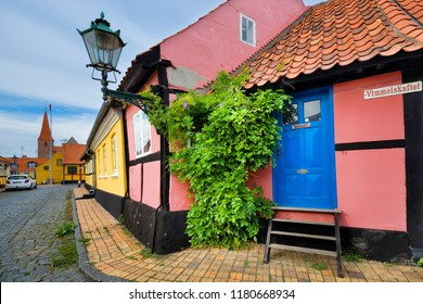 RONNE, DENMARK - AUGUST 19, 2018: View of traditional colorful half-timbered houses at cobblestoned street called Vimmelskaftet - Bornholm's smallest house in the foreground
