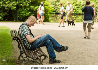 RONNEBY, SWEDEN - JULY 06, 2014: Male person in tattered clothes and sad posture sitting on bench having a smoke.