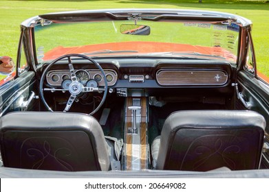 """RONNEBY, SWEDEN - JULY 17, 2014: Press show for upcoming event """"Pony and muscle car meet"""". Interior of red Ford Mustang 1966 as seen from behind."""
