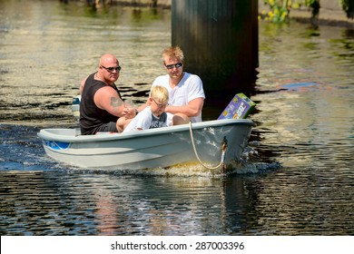 RONNEBY, SWEDEN - JUNE 13, 2015: Sillarodden, a public rowing contest from sea to town to sell herring. Three persons in small motor boat on the river seen face on.