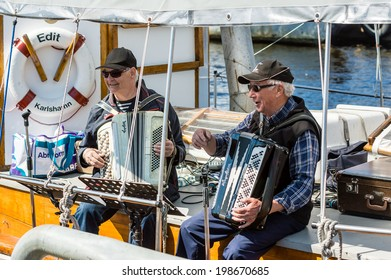 RONNEBY, SWEDEN - JUNE 14, 2014: Sillarodden, a local event with competing teams of fish mongers. Two men playing the accordion on fishing boat.