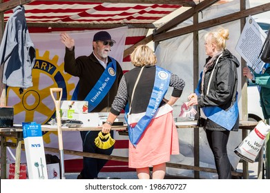 "RONNEBY, SWEDEN - JUNE 14, 2014: Sillarodden, a local event with competing teams of fish mongers. Rotary members having a lottery. Banner: ""Eradicate Polio Now"" in swedish."