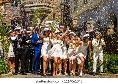 Ronneby, Sweden - June 15, 2018: Upper secondary school graduation day. Happy students standing together with party poppers and confetti in the air.