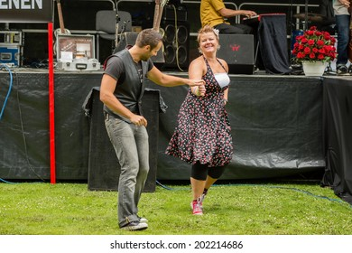 RONNEBY, SWEDEN - JUNE 28, 2014: Nostalgia Festival, classic cars, motorcycles, fashion and entertainment. Dancers dressed in old times clothing performing at carshow.